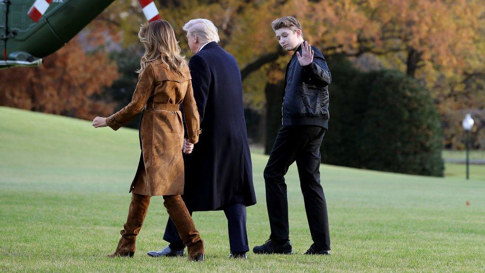 メラニアとドナルド・トランプと一緒に歩きながら手を振っている、真っ黒なバロン・トランプ