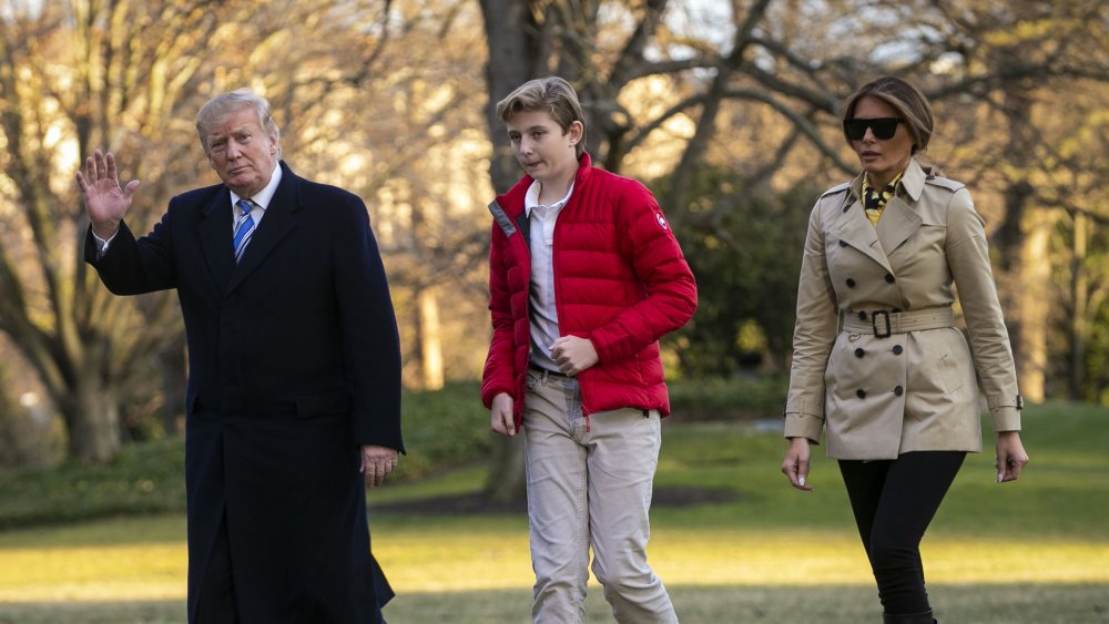 外でバロンとメラニア・トランプと一緒に歩きながら手を振っているドナルド・トランプ