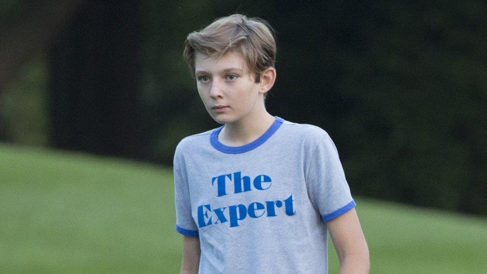 青いTシャツを着て外を歩くバロントランプ