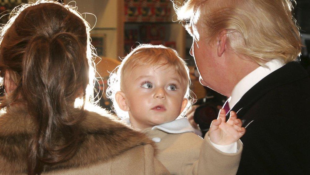 ドナルド・トランプの隣に赤ちゃんバロン・トランプを抱いているメラニア・トランプ