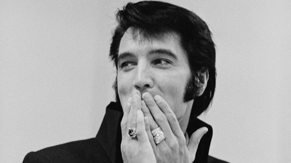 指輪を身に着けていて、もみあげが手で口を覆っているエルビス・プレスリーの白黒写真