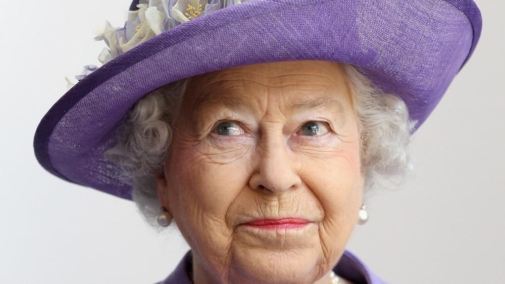 エリザベス女王が帽子をかぶってポーズをとる