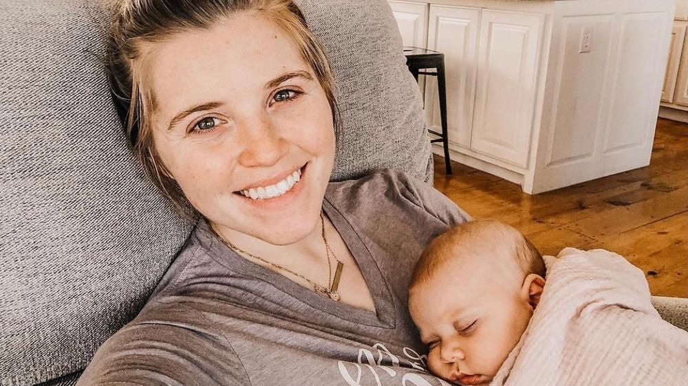ジョイ・アンナ・ダガー、自撮り写真、化粧なし、お団子の髪、眠っている赤ちゃんを抱っこ