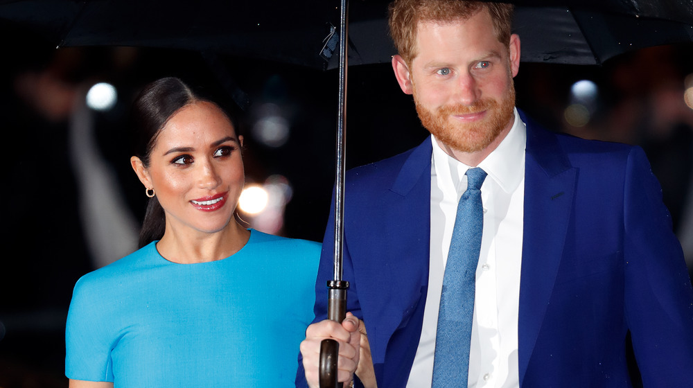 メーガン・マークルとハリー王子がイベントで傘の下に立つ