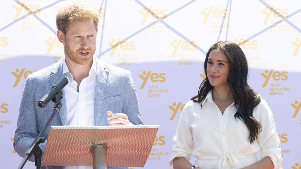 メーガン・マークルの隣の表彰台で話すハリー王子