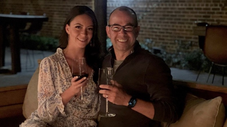 ワイングラスを持って微笑むメリッサ・デイヴィスとジェームズ・マレー